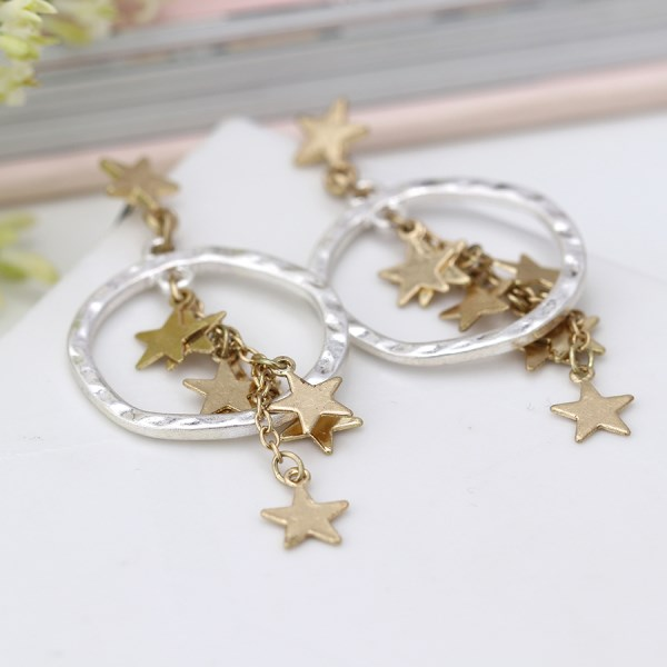 Worn gold multi star cluster and silver hoop earrings | Image 1