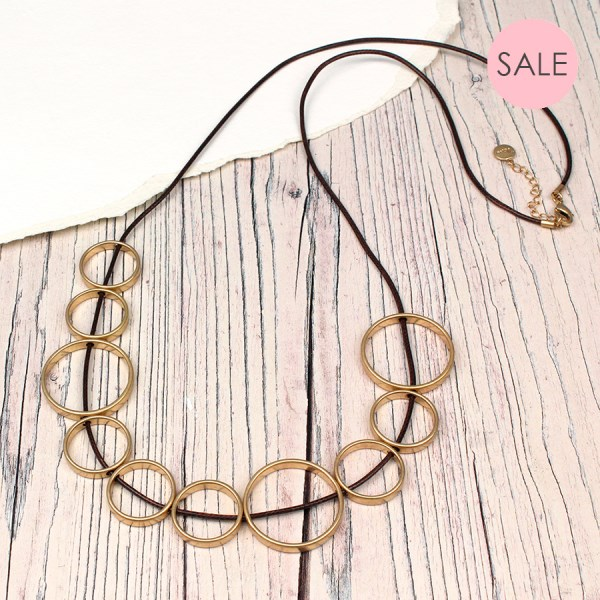 Golden circles necklace on long dark cord | Image 1