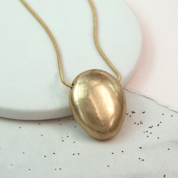 Golden oval shaped pebble necklace with a worn finish | Image 1