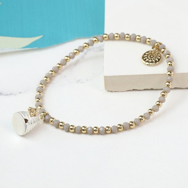 Grey bead bracelet with a silver and gold beehive charm | Image 1