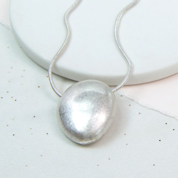 Silver plated oval pebble necklace with a worn finish | Image 1
