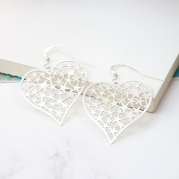 Silver plated scratched heart earrings filled with stars | Image 1