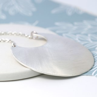Silver plated scratched crescent pendant on a long chain | Image 3