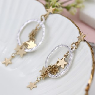 Worn gold multi star cluster and silver hoop earrings | Image 3